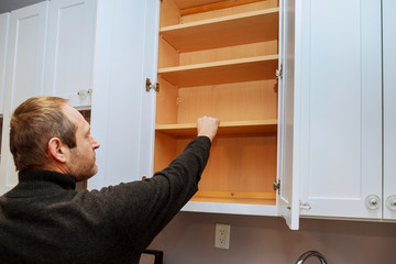 Closeup of a cabinet installer installing hardware on new kitchen cabinets.
