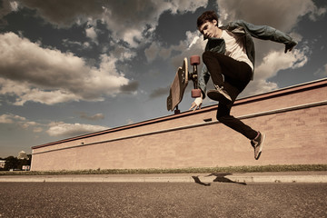 People, leisure, hobby, recreation and active lifestyle concept. Picture of flying guy in the air with longboard while doing tricks during every day practice in cityscape. Warm filter, toned image