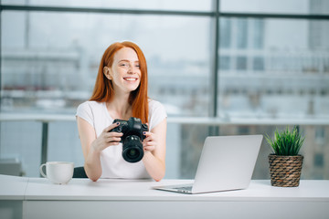 redhead girl photographer is viewing images on camera