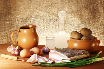 A moonshine bottle, bread with lard, potatoes and egg. Rustic style.