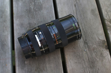 Vintage camera lense on wooden boards - pictured from above