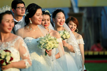 Chinese brides pose for photographs during the mass wedding ceremony for fifty Chinese couples in Colombo