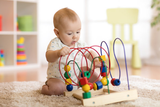 baby playing with educational toy in nursery
