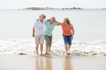group of three senior mature retired women on their 60s having fun enjoying together happy walking on the beach smiling playful