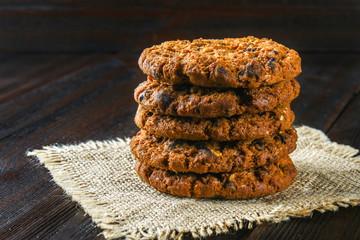 Homemade oatmeal cookies. A stack of sackcloth on a brown wooden table.