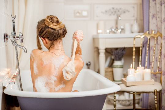 Young woman washing with brush in the beautiful vintage bath full of foam in the bathroom decorated with candles