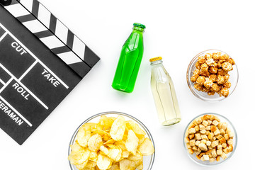 Fast food for watching film. Crisps, popcorn, rusks, drinks near clapperboard on white background top view