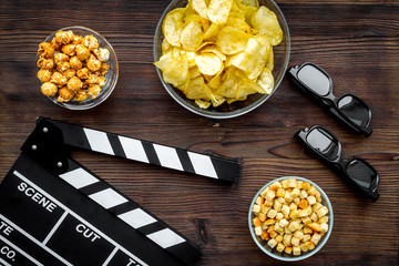 Crisp, popcorn, rusks for watching film. Clapperboard and glasses on dark wooden background top view