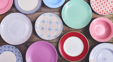 Set of different colorful dishes over wooden board. Space for text