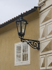 close up old street lamp lantern on renassaince palace yellow white facade in prague castle