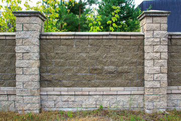 The texture of a stone fence with rectangular blocks and concrete seams.