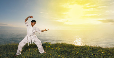 Kid training karate on the nature. Beautiful sea and sunset sky on background.  Wide banner edition.