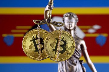 Symbol of law and justice, physical version of Bitcoin and Swaziland Flag. Prohibition of cryptocurrencies, regulations, restrictions or security, protection, privacy.
