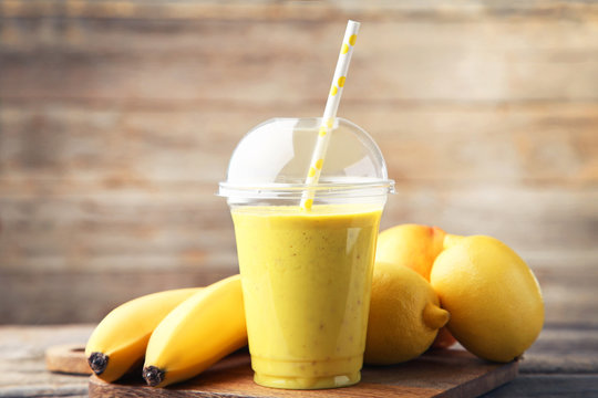 Yellow smoothie in plastic cup with bananas and lemons on wooden table