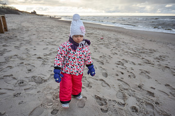Little girl wear jacket and hat walk is playing at the beach near baltic sea on cloudy sky in winter time