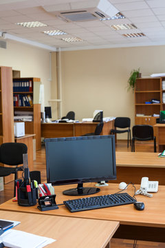 Work place with off lcd monitor of computer, keyboard and mouse are on table in empty room