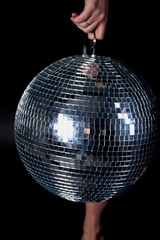 Disco ball in the hands of a woman. A symbol of music, clubs and nightlife. Holidays and fun parties