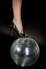 Disco ball , it female foot in shoes . A symbol of music, clubs and nightlife. Holidays and fun parties