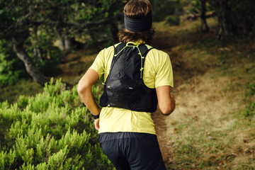Back view of a ultra trail runer running on a forest close to Collado Jermoso, Leon, Spain