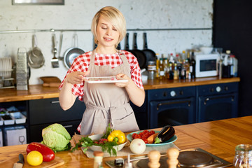 Portrait of smiling young woman taking photo of vegetables on kitchen counter to share on social media, copy space