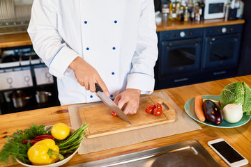 Close up of unrecognizable cook cutting fresh cherry tomatoes and other vegetables with chef knife while working in modern kitchen, copy space