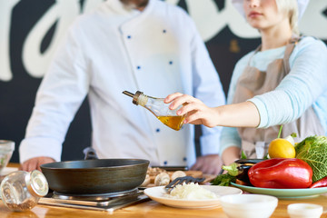 Close up view of young woman adding olive oil to gourmet dish while working with professional chef in restaurant kitchen