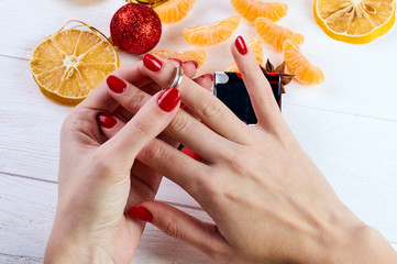 The girl tries precious ring on a hand with a red manicure. A beautiful ring of gold with precious stones. A gift for Christmas, birthday, St. Valentine's Day, Mother's Day, wedding, engagement.