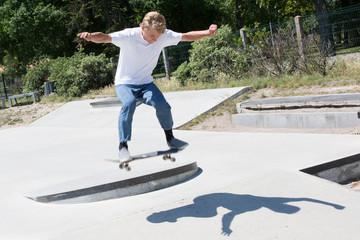 young boy blonde teenager skating in skatepark