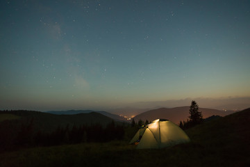 A summer night a tent in the mountains stands under the stars.
