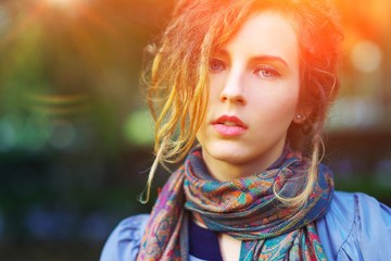 Portrait of young beautiful successful girl in scarf outdoors, closeup