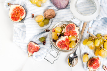 Autumn breakfast ideas, recipes. Jar of overnight autumn oats with red figs, grapes and walnuts. On white marble table, copy space top view