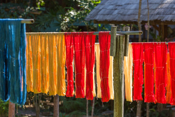 Colorful fabric hanging to dry after traditional dye processshot in Luang Prabang, Laos