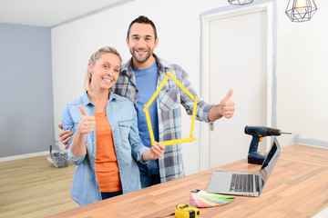 cheerful young couple making future project and renovating new home thumbs up