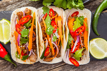 Three mexican tacos with meat and vegetables. Tacos al pastor on