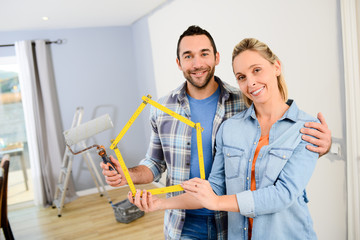 cheerful young love couple in new house painting and decorating their home wall