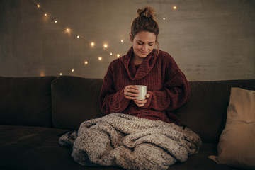 Relaxed woman drinking coffee in winter at home