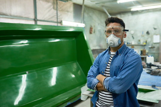 Portrait of handsome workman wearing protective goggles and mask  posing confidently with arms crossed in painting workshop, copy space
