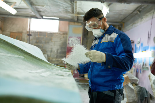 Portrait of mature man wearing protective mask repairing boat while working in yacht workshop, copy space