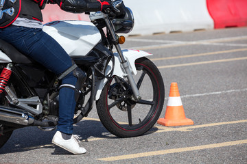 Close up view at training motorbike with person practicing on motor-vehicle proving ground
