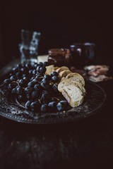 Red grapes and slices of bread on old fashioned silver plate