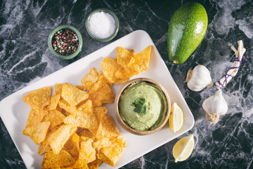 Arrangement Of Nachos (Corn Chips) And Guacamole (Avocado Sauce) On A Marble Surface