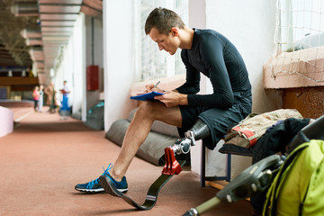 Young amputee athlete sitting on bench in gym and writing