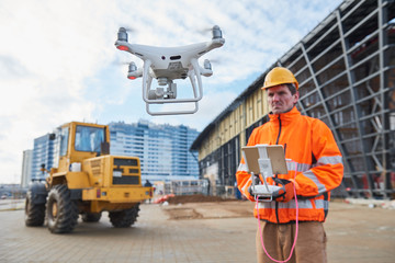 Drone operated by construction worker on building site Wall mural