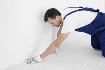Worker rolling out foam film on floor before carpet installation