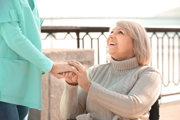 Senior woman and young caregiver holding hands outdoors