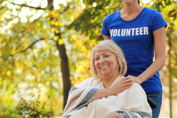 Senior woman and young volunteer in park