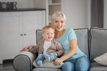 Attractive young mother with her baby on couch at home