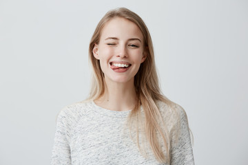 Gloomy young blonde woman with dyed hair dressed casually making faces at camera, blinking, sticking out her tongue. Positive girl having fun indoors