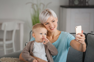 Young mother taking selfie with her baby at home