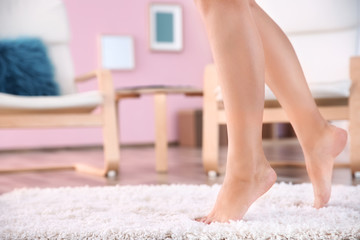 Legs of young woman walking on soft carpet at home